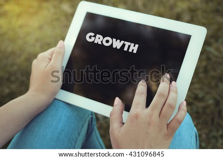 Young women holding tablet writen Growth on it - stock photo