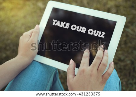 Young women holding tablet writen Take Our Quiz  on it - stock photo
