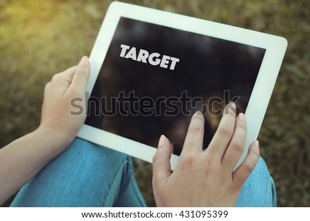 Young women holding tablet writen Target on it - stock photo