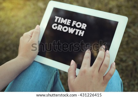 Young women holding tablet writen Time For Growth on it - stock photo