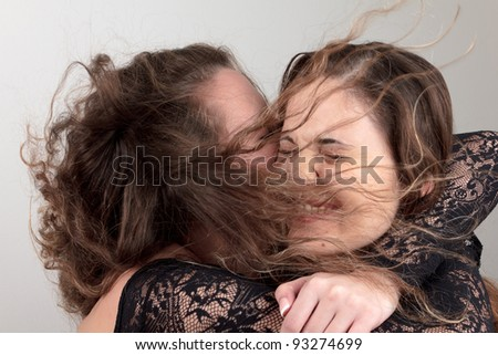 Young women hugging with wind in their hair
