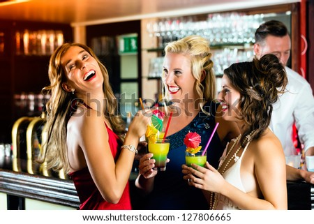 Young women in bar or club having fun and laughing - stock photo