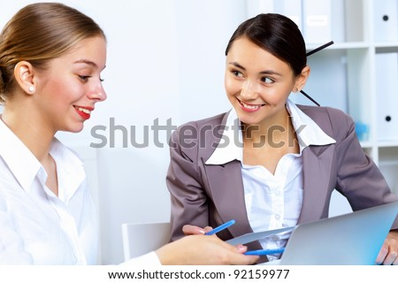 Young women in business wear working in office together