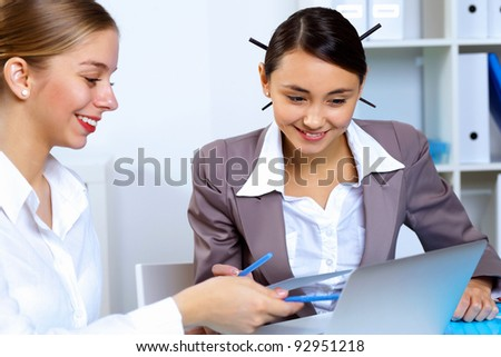 Young women in business wear working in office together - stock photo