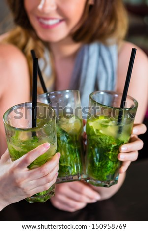 Young women in cafe, bar or restaurant, drinking cocktails and enjoying the leisure time - stock photo
