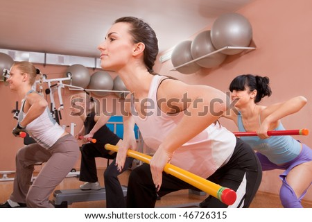 Young women in gym doing exercises with fitness sticks - stock photo