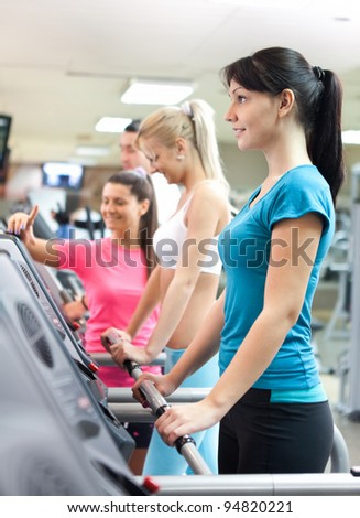 young women in gym on running machine with personal trainer - stock photo