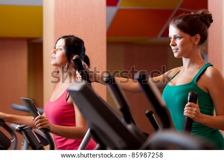 Young women in gym on stepper machine - stock photo