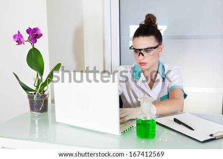 Young women in laboratory using a laptop  - stock photo