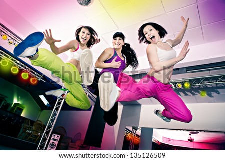 young women in sport dress at an aerobic and zumba exercise - stock photo