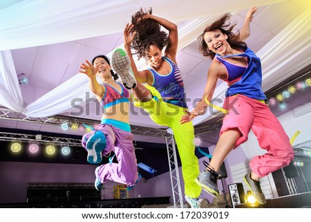 young women in sport dress jumping at an aerobic and zumba exercise - stock photo