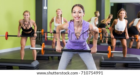 Young women in sportwear training with barbell workout at health club