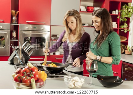 Young women in the kitchen - stock photo