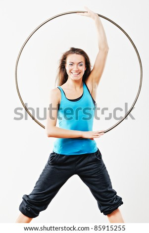 Young women in tracksuit with hula-hoop in studio - stock photo