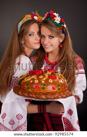 Young women in ukrainian clothes, with garland and round loaf - stock photo