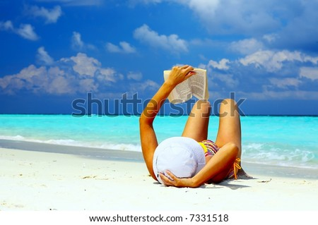 Young women is reading on the coral beach, Maldives - stock photo