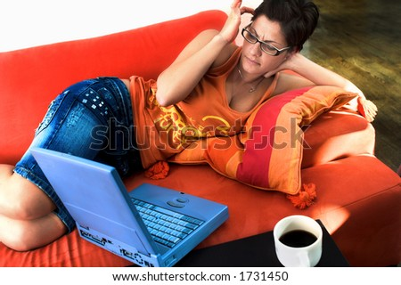 Young women is resting on the couch at home and working on a laptop computer. She looks troubled. - stock photo