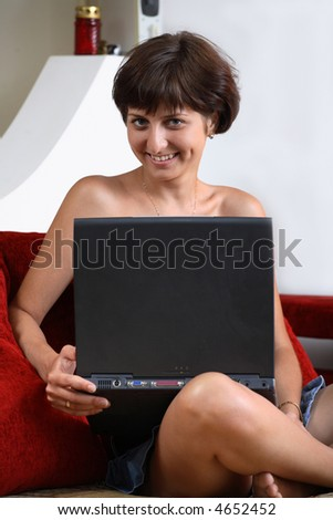 Young women is resting on the couch her laptop computer. - stock photo