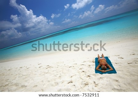 Young women is sunburning on the coast of the Indian Ocean, Maldives - stock photo