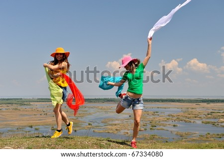 young women jumping on field in summer