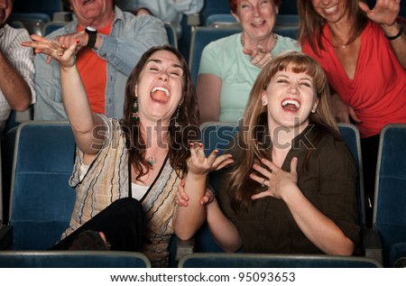 Young women laugh out loud in theater - stock photo