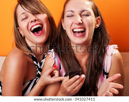 Young women laughing when looking at a cellphone