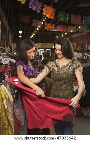 Young women looking at colorful clothing while shopping. Vertical shot. - stock photo