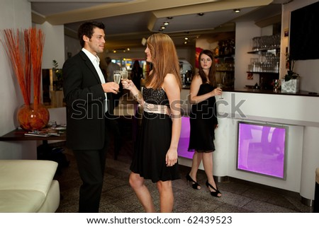 Young women looking at couple. Focus on glasses - stock photo