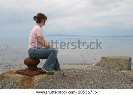 Young women looking at the St-Laurent river at tide down. - stock photo
