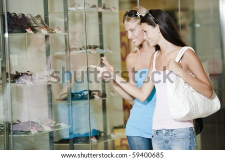 Young women looking through shop window - stock photo