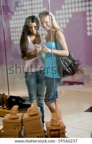 Young women looking through shop window - stock photo