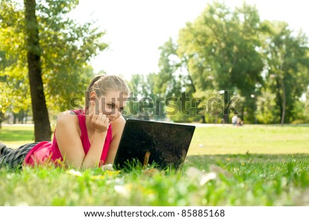 Young women lying on grass in park and using laptop - stock photo