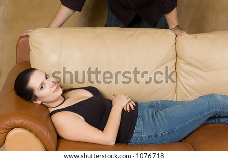 young women lying on the couch, man hands behind