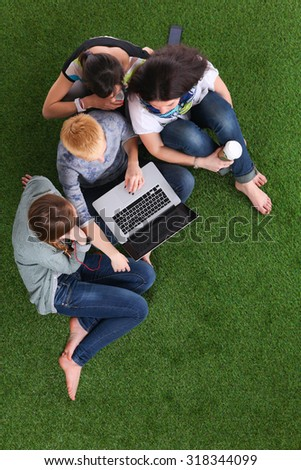 Young women lying on the grass using a laptop together   - stock photo