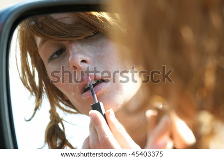Young women made up, looking in the mirror of the car - stock photo