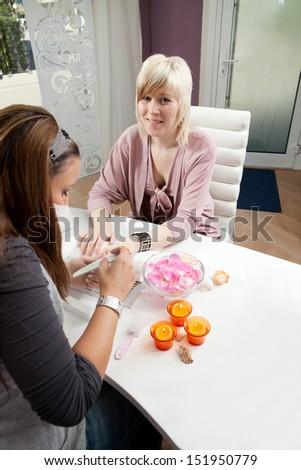 Young women making fingernails at beauty salon - stock photo