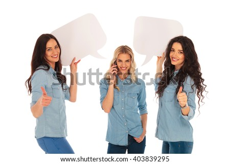 young women making the ok thumbs up hand sign and holding speech bubbles while their firend is talking on the phone on white background - stock photo