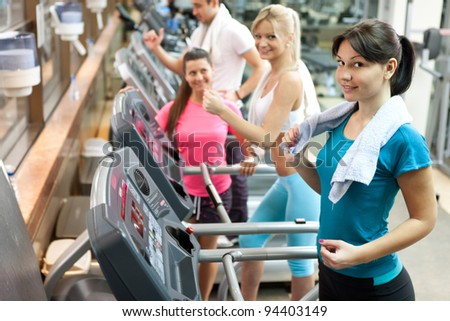 young women on treadmill at gym - stock photo