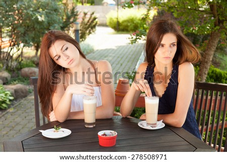 Young women outdoors sitting in terrace cafe with coffee.