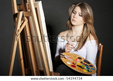 young women painter with easel on dark background - stock photo