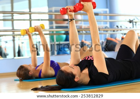 Young women performing aerobics exercise with dumbbells in a gym - stock photo