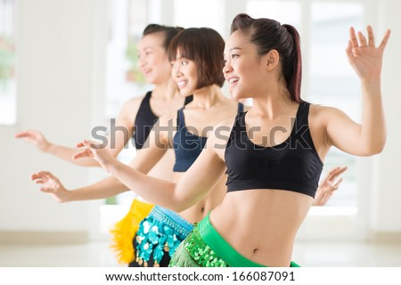 Young women performing belly dance in a dance studio on the foreground - stock photo