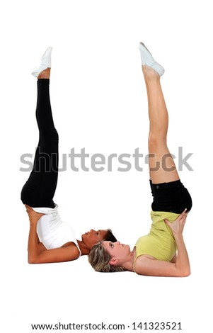 Young women performing shoulder stands - stock photo