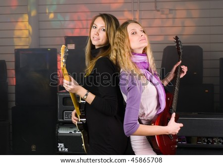 Young women playing music on guitars at concert