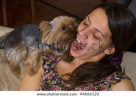 Young women plays with a terrier puppy on a coach