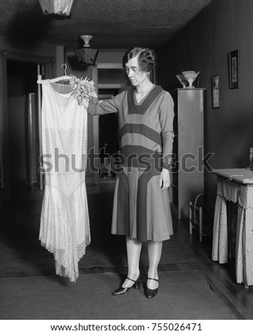 Young women quizzically evaluating new dress, May 14, 1925.