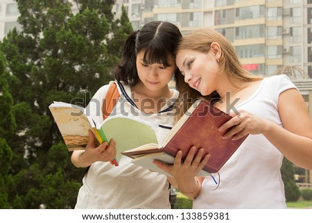 Young women reading book in the green park. Students are studying, learning outdoor - stock photo