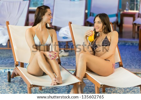 Young women relaxing by the pool - stock photo