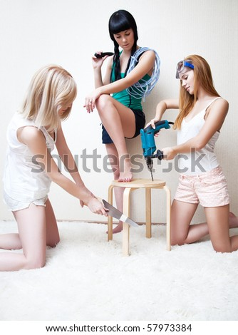 Young women repairing stool. Bright white colors. - stock photo