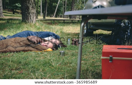 Young women resting in sleeping bags on campsite - stock photo